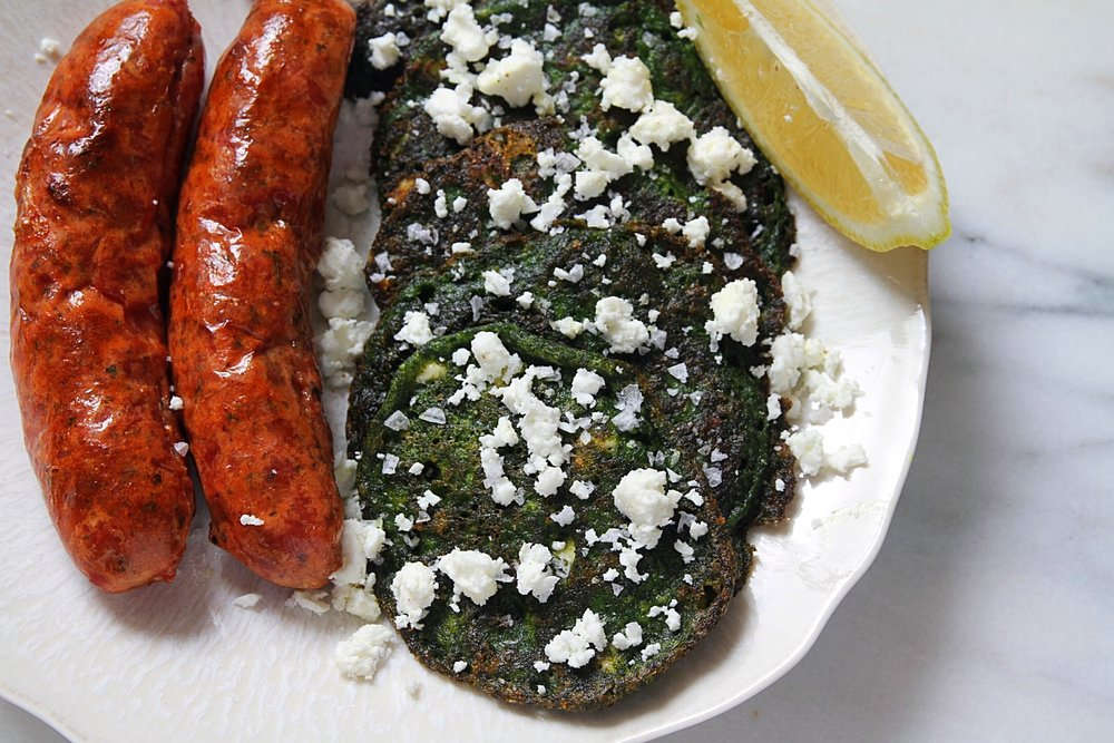 Swiss chard fritters topped with feta, served with chicken sausage.