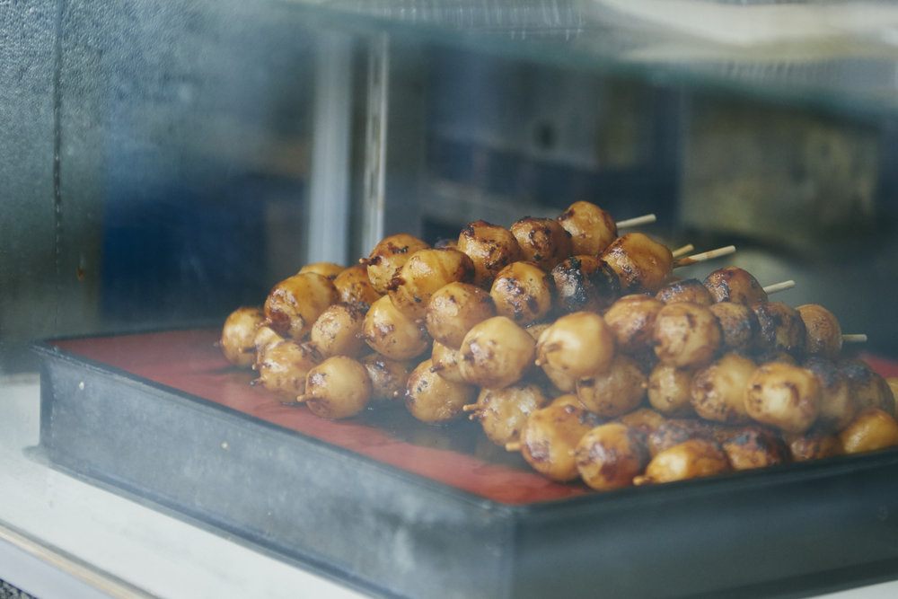 Freshly grilled mochi dipped in locally made soy sauce!