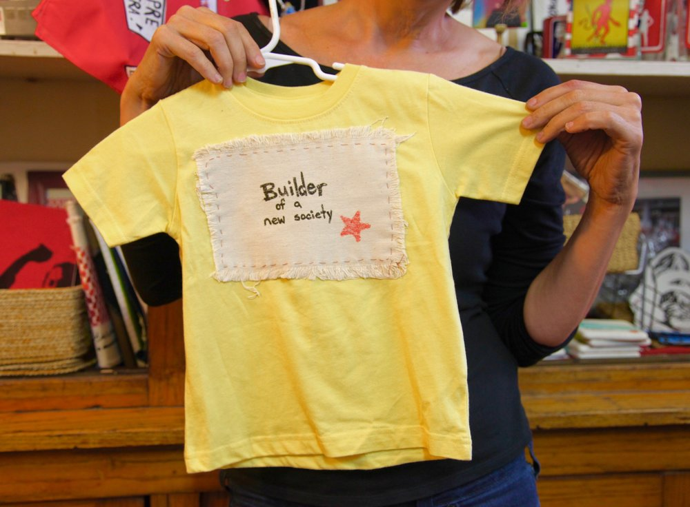 """The whole store really looks forward and positive … That's one of the reasons you're seeing a lot of baby clothes. Babies are the future."" Stephanie noticed that many people are wary of politicizing children. But she sees it as a ""playful and fun way to share political culture."" With her array of shirts with slogans like ""Builder of a new society,"" Stephanie hopes to show her belief that it's possible to raise kids progressively and politically."