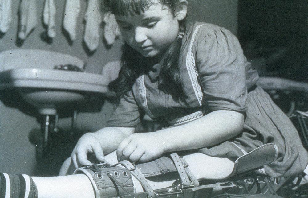 Girl-adjusts-polio-braces-(deleted-4db4a6d2-9cadf0-07f36fb8).jpg