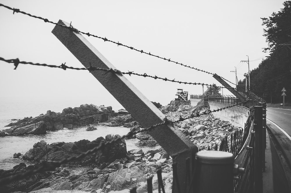 The further north I walked, the more my views of sandy beaches & rocky coastline were framed by barbed wire & dotted with observation posts. The posts seemed to have been abandoned, and the fences were often decaying & rusting.