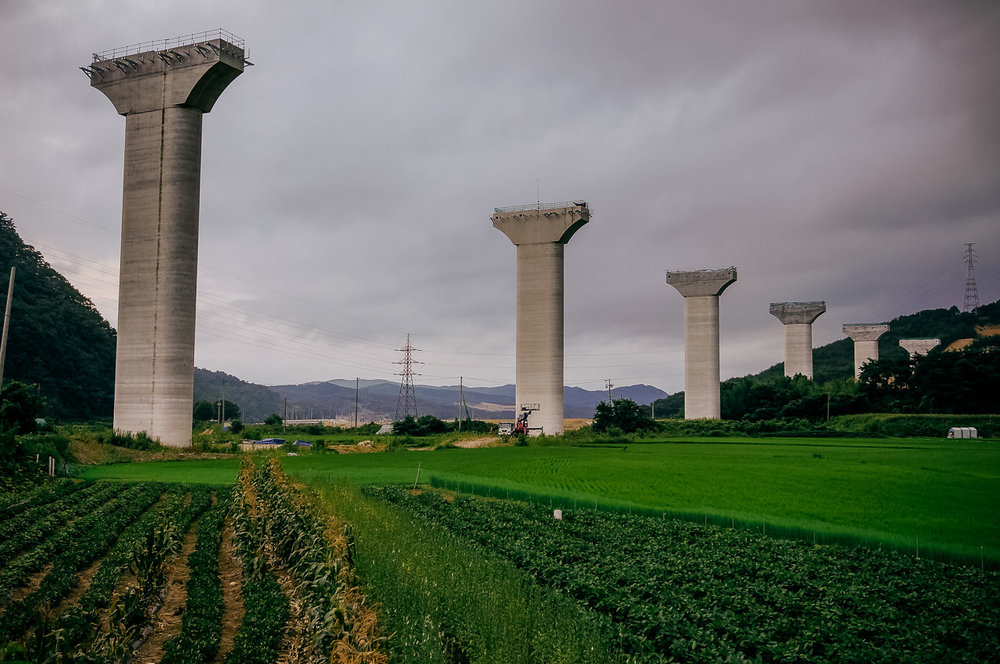 After a brief detour inland towards Gyeongju, I cowboy-camped beneath this surreal highway construction project at the base of the pillar on the left - & woke to find a sour-faced farm lady staring down at me.