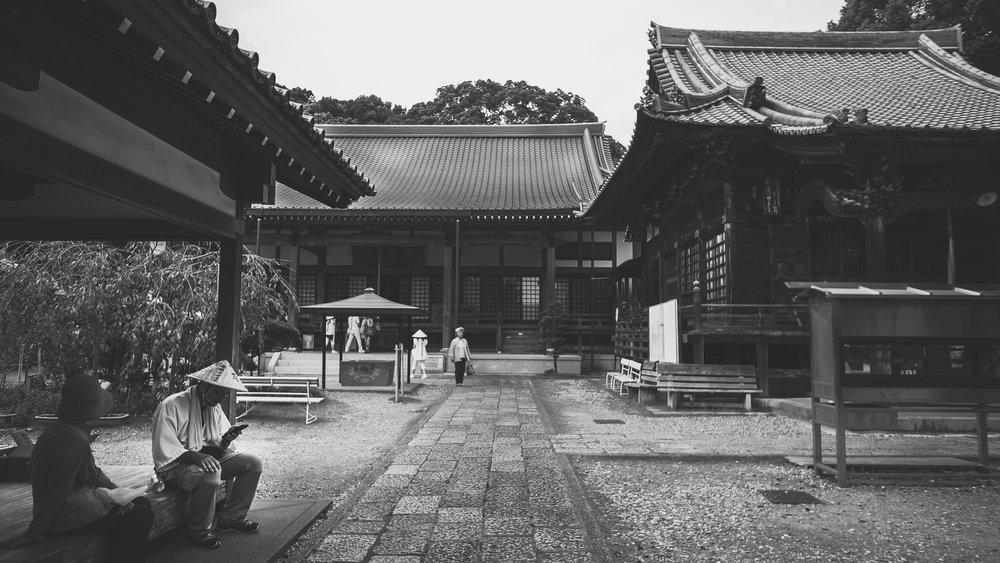 Day 32: A Henro texting at Sekkei-ji, Kochi, #33 on the circuit.