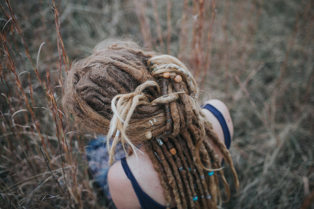 4. Half up Dread Knot    Taking 2 handfuls of dreads from each size pull back and tie a knot.    You can tuck in any ends of your dreadlocks that stick out.