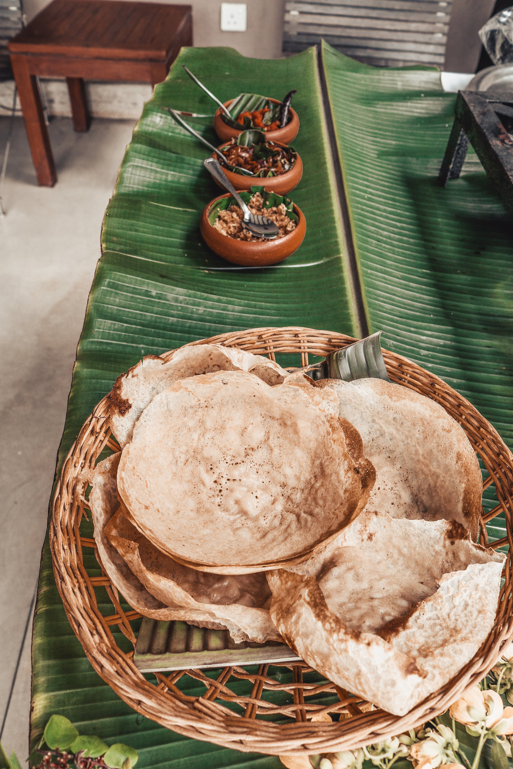 Traditional Sri Lanka food experience by Mount Havana - Traditional Sri Lanka food experience by Mount Havana - One of the most popular and traditional food in Sri Lanka are hoppers (called appa as well) in the shape of bowl. They are usually served for breakfast or dinner. One of the most popular ones comes with the egg cooked into the center of the bowl-shaped hopper. You can fill the hopper with the rest of their typical add-ons such as sambar (similar to vegetable stew), sambol (coconut, onion and cilli) served in small multiple dishes. Roll it and eat it. Cooked and served right there on a terrace with a view - it can't get better than this. Hopefully you do like spicy, cause Sri Lanka is all about that.