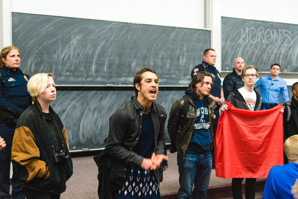 Conservative commentator and columnist Ben Shapiro looks on as a group of UW Madison students attempt to shut down a speaking engagement