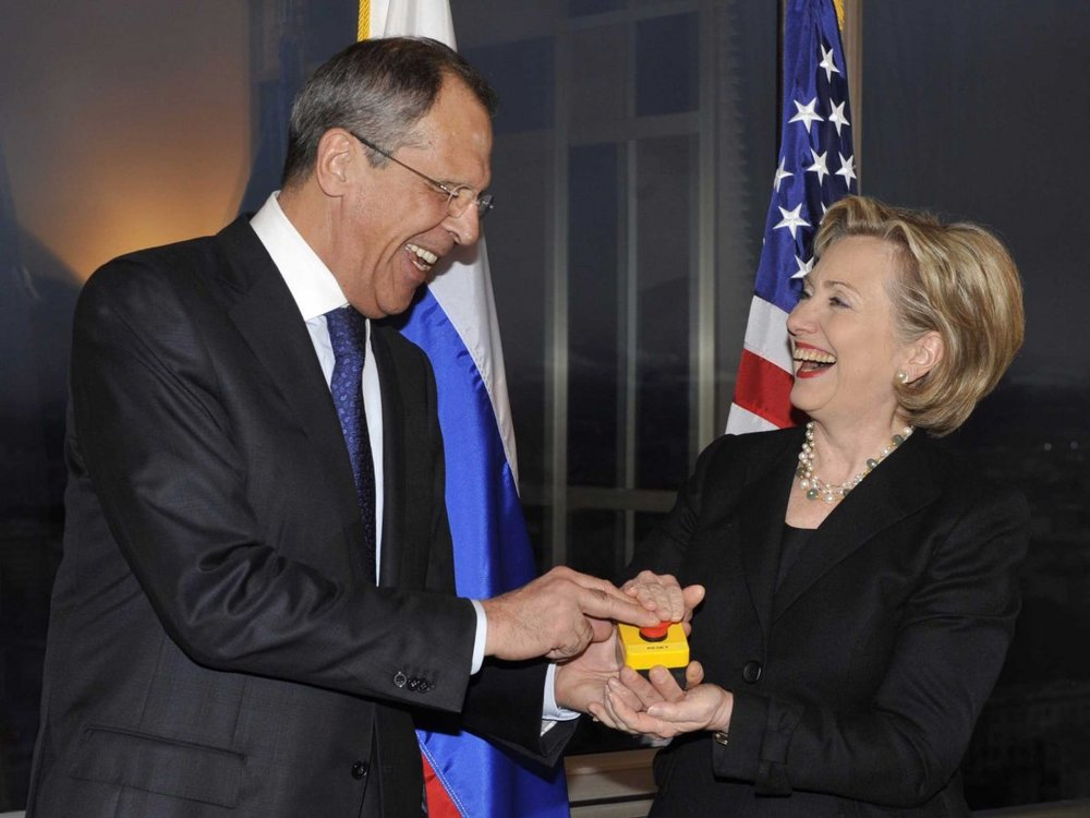 """Then-Secretary Clinton and Russian Foreign Minister Sergey Lavrov press a ceremonial """"Reset Button"""" for US-Russian Relations"""