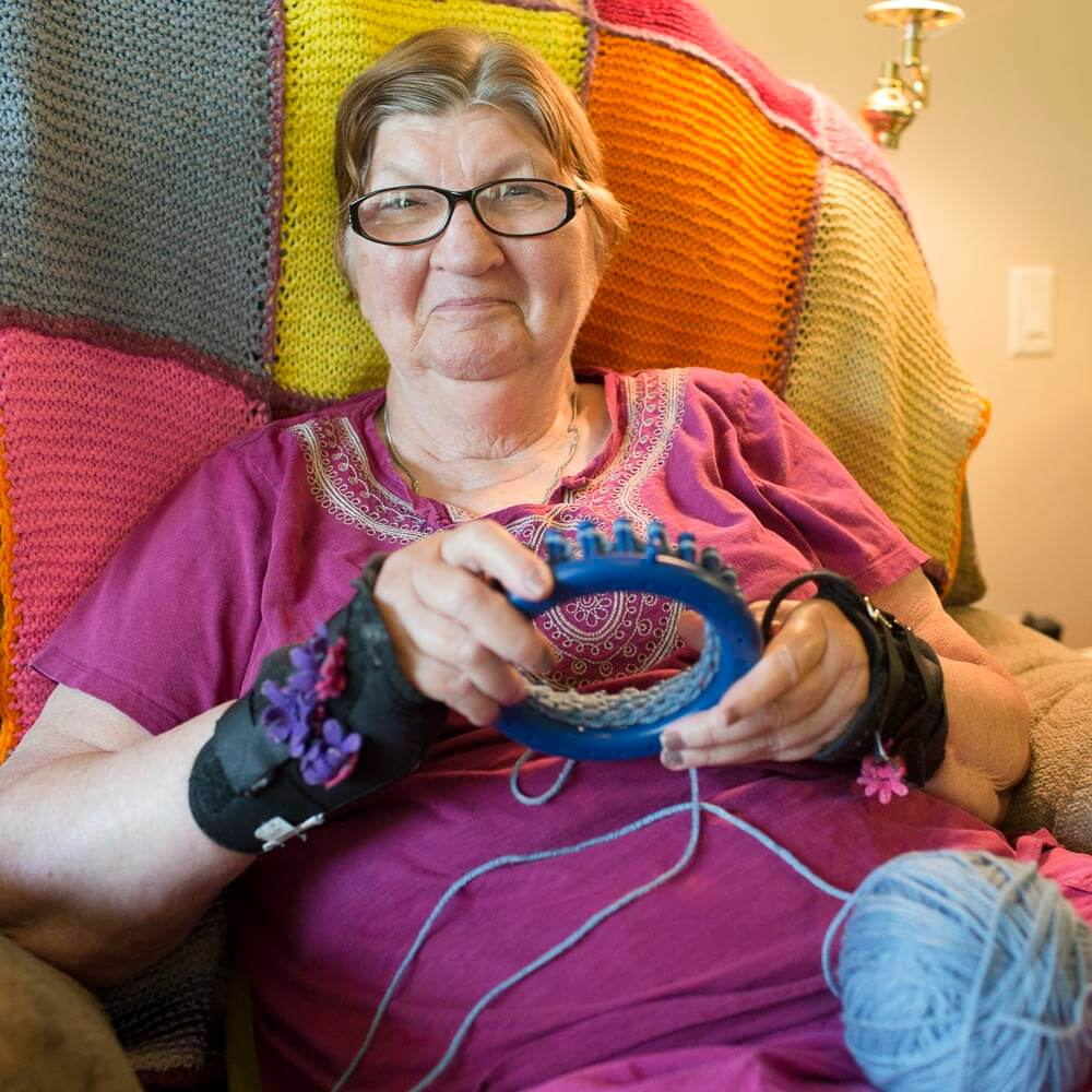 Donna enjoys knitting in her living room.