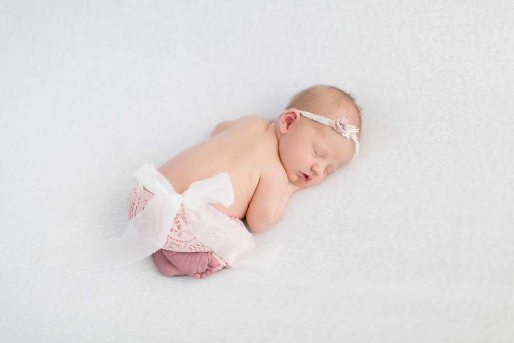 newborn baby with pink pants and white bow.jpg