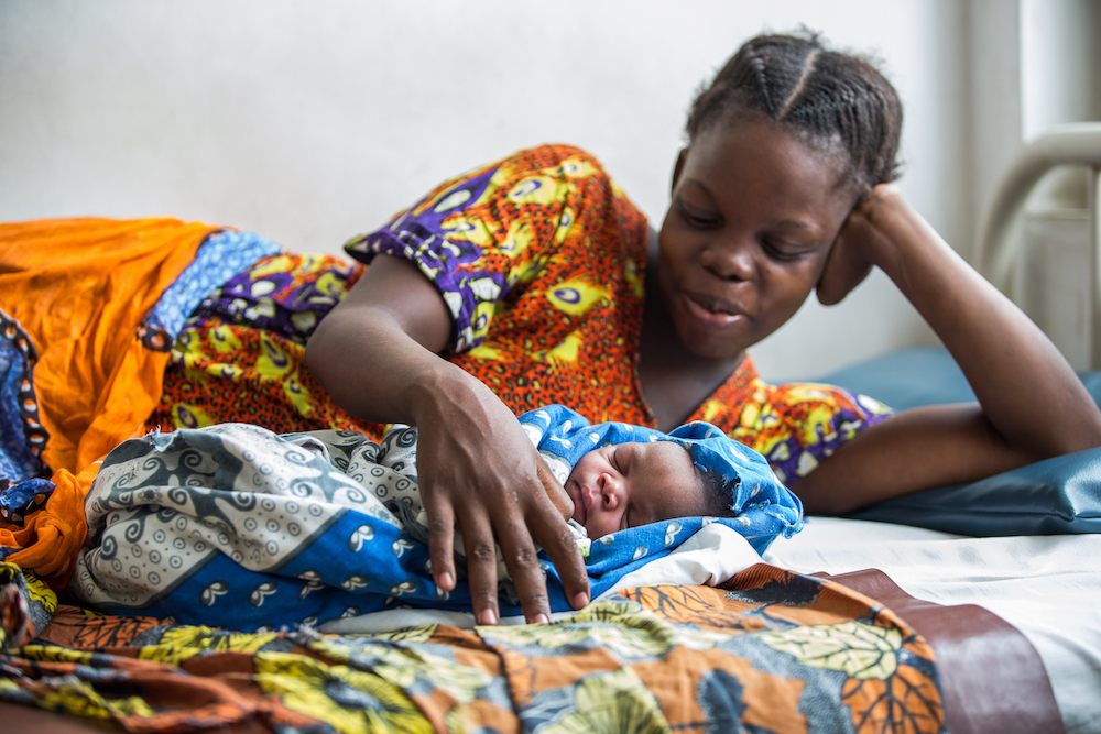 Esther resting with her newborn baby. Photo Credit: Sala Lewis