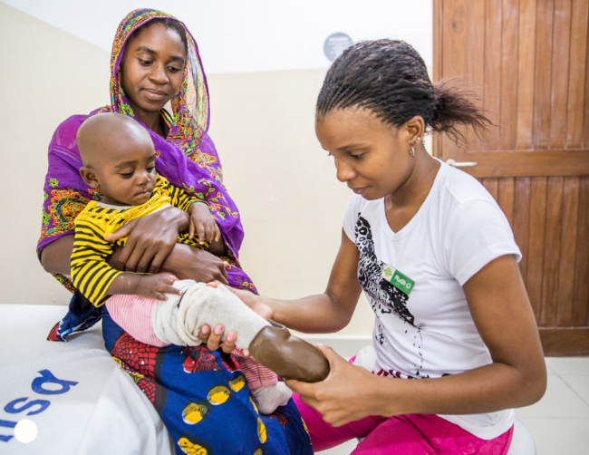 A young girl being fitted with a prosthesis at CCBRT. Photo credit: Sala Lewis