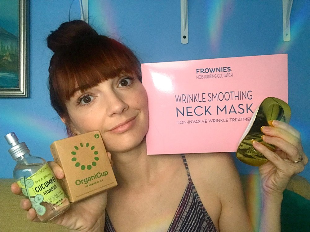 Jackie Johnson with her favorite products of the week of August 27: Frownies Neck Mask, OrganiCup, Shea Brand Cucumber Hydrosol, and Ikoo hairbrush.