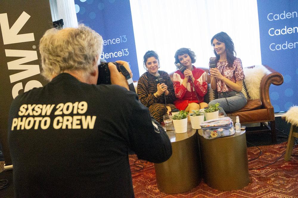 Jess Rona, Milana Vayntrub, and Jackie Johnson being photographed.