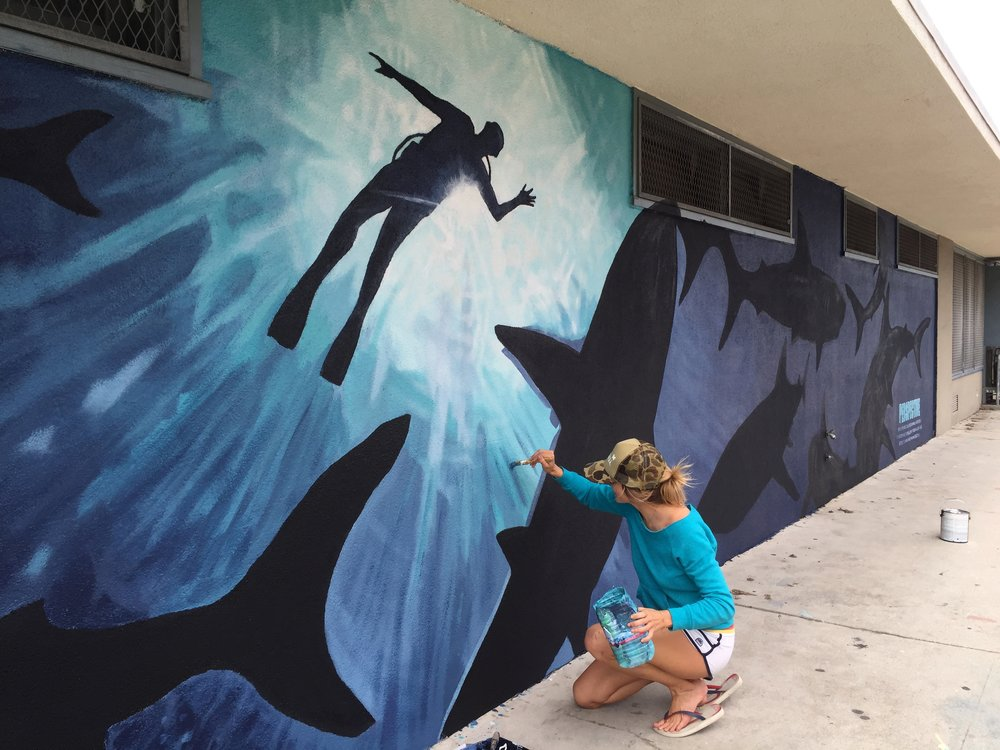 Greta Kruesi putting finishing touches on the shark mural.