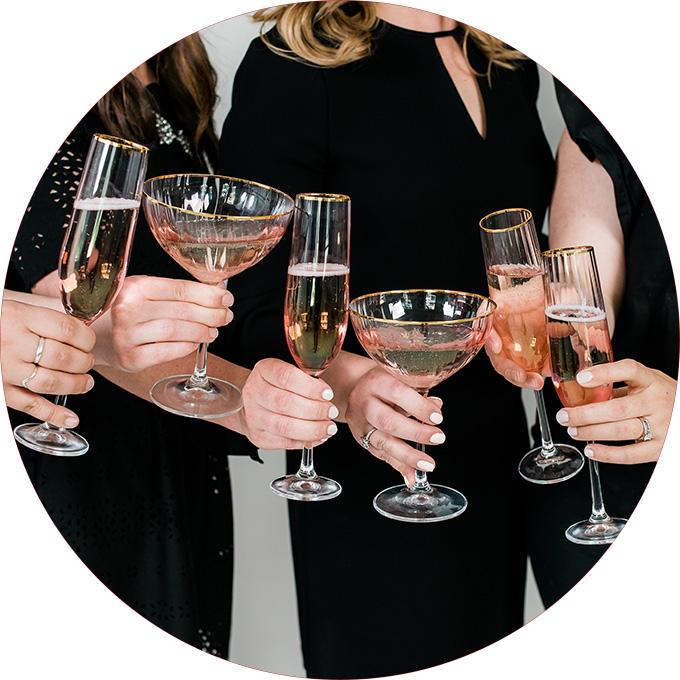 Women in black dresses holding champagne glasses for small business branding shoot with Seattle Branding Photographer Rebecca Ellison.