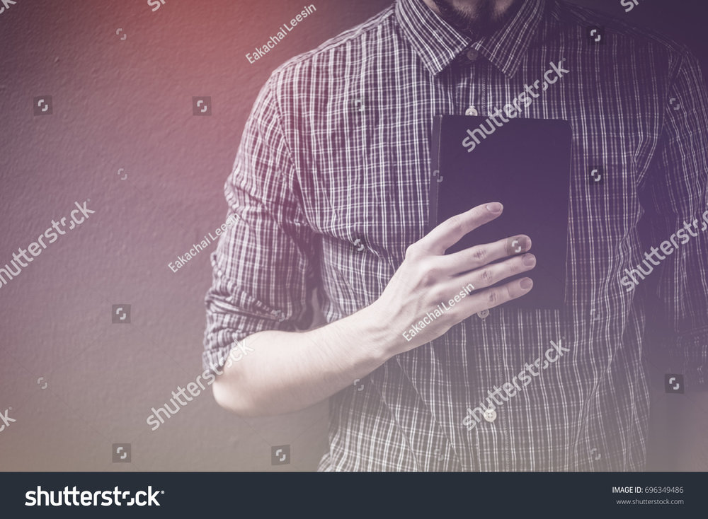 stock-photo-closeup-on-a-man-holding-a-bible-at-shopping-mall-believe-concept-696349486.jpg