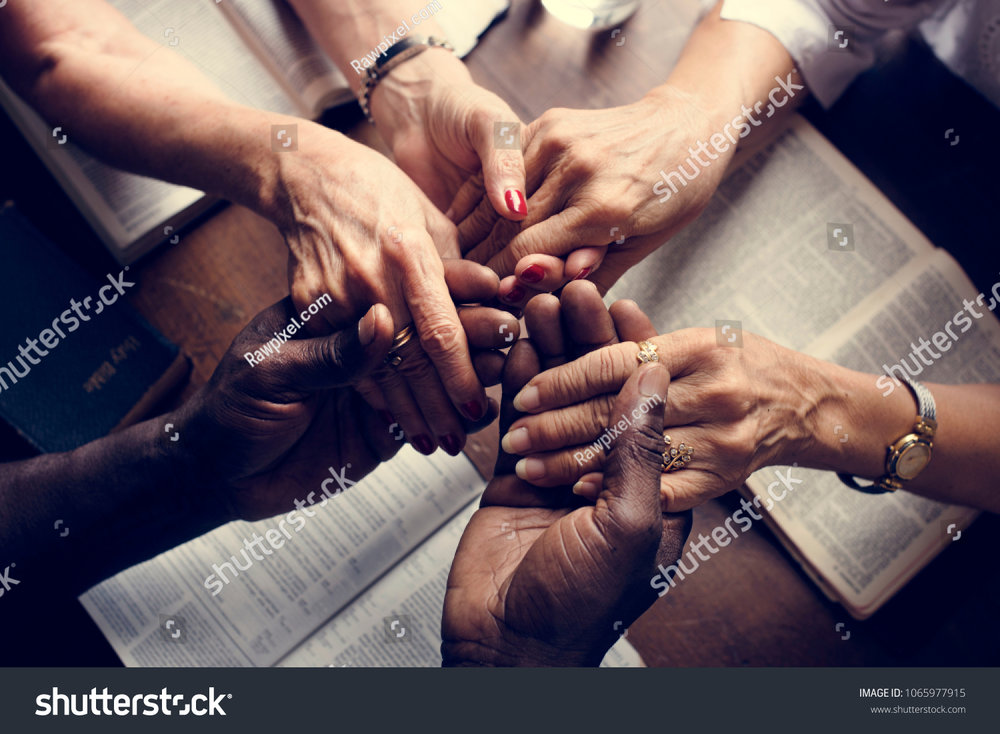stock-photo-group-of-people-holding-hands-praying-worship-believe-1065977915.jpg