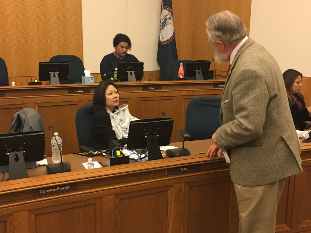 Tran talks with a lobbyist while nursing during a hearing. Tyone Turner / WAM