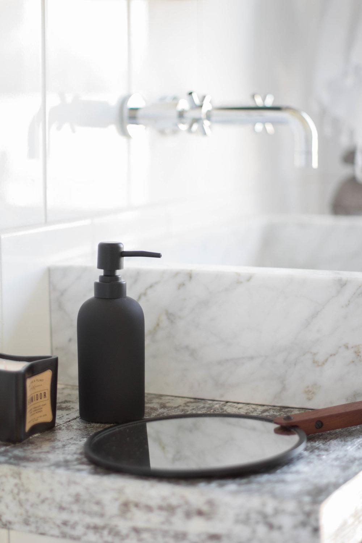 KOA HOUSE_pool bathroom black and white wall mount faucet marble blck sink hand mirror.jpg