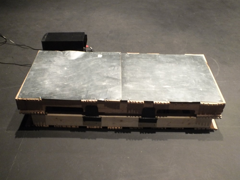 The Rack  – based on the name and look of an 18th century torture device of the same name in which a victim's limbs are tied down to be cut with swords, smashed with hammers, or stretched (Scott 1959).  The   Rack  is a small rectangular box with a metal surface amplified with contact mics that are fed through two custom designed circuits. The two circuits are also fed through the same output which allows creates a feedback loop that falls into chaotic sounds when interrupted by sounds on the metal surface. During rehearsals for the work I captured sonic dancer Richard Lee experimenting with  The Rack  which can be seen here: