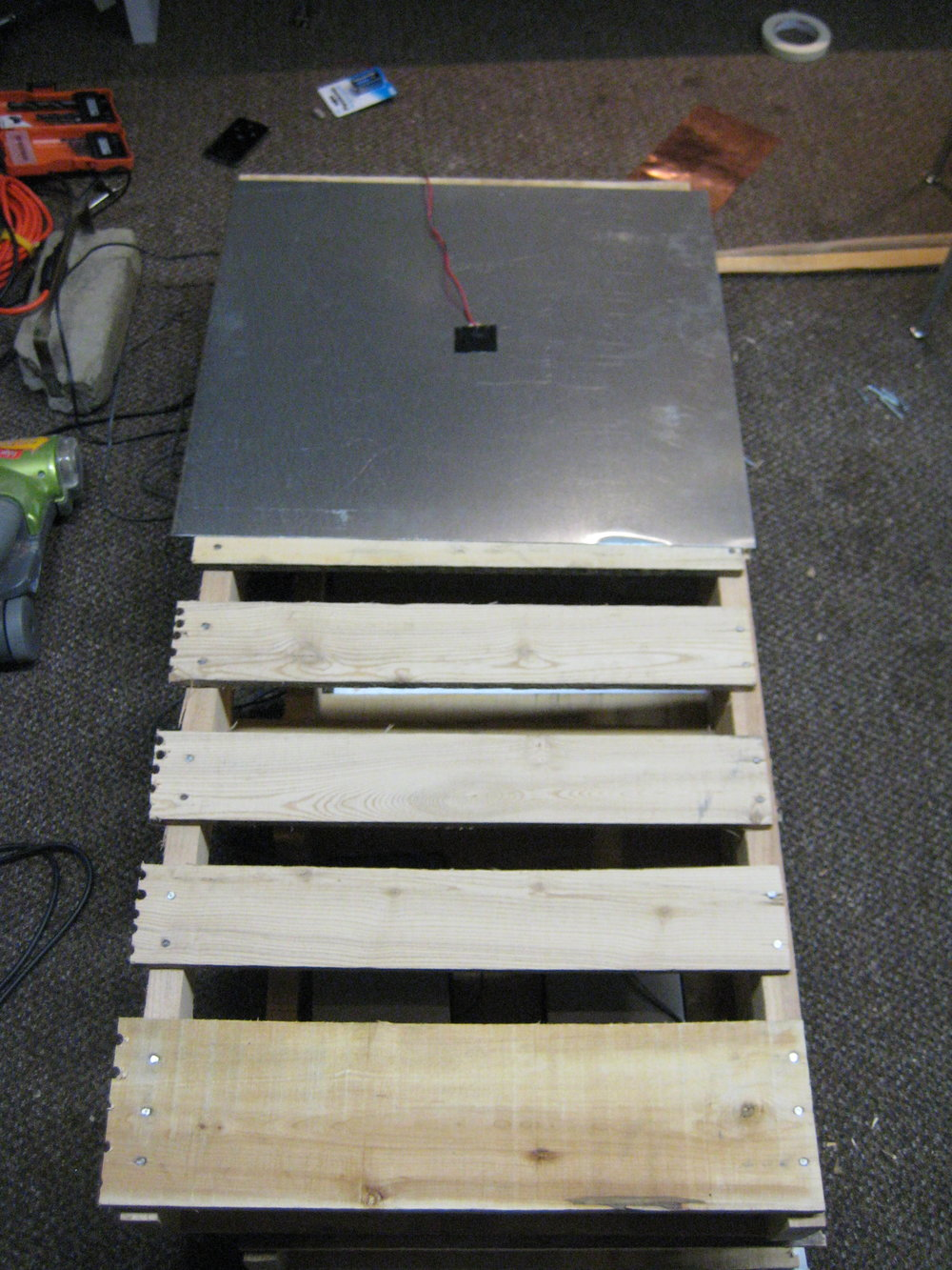 The next phase of construction was to create a durable casing that could withstand violent movements from a dancer. My solution was to encase the electronics in a docking palette covered in sheet metal. The first step of this process was to cut a docking skid in half andplace one half of the skid on top of the other.  I then attached a piezo microphone to the sheet metal and plugged it into the input of the circuit, placing the speakers directly underneath the sheet metal that is attached to the piezo microphone