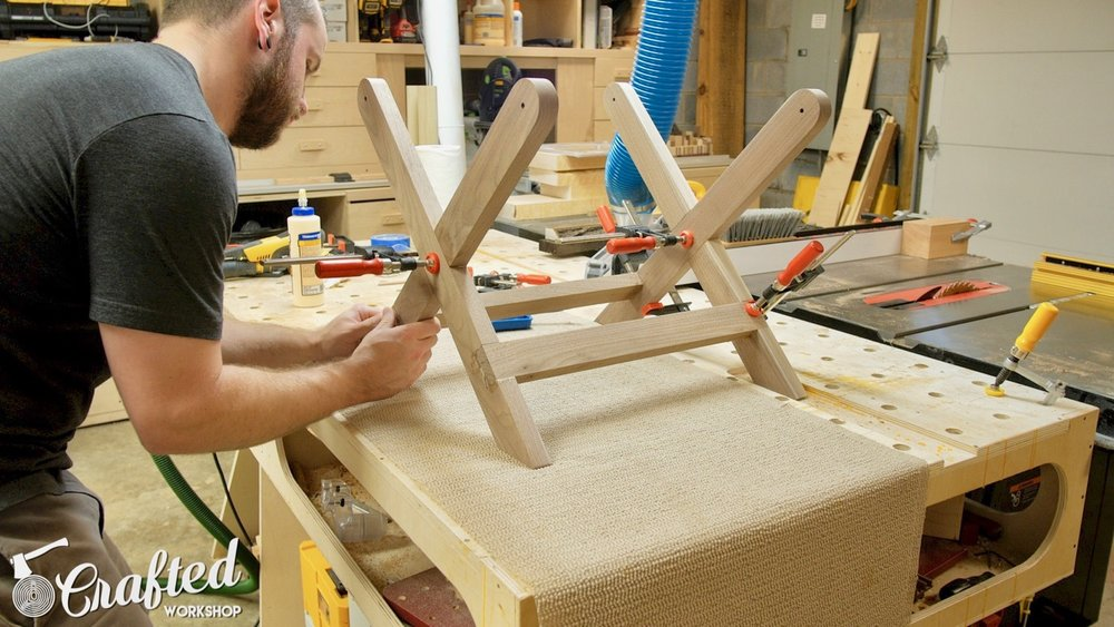 Gluing up the Walnut stool base using Bessey clamps.