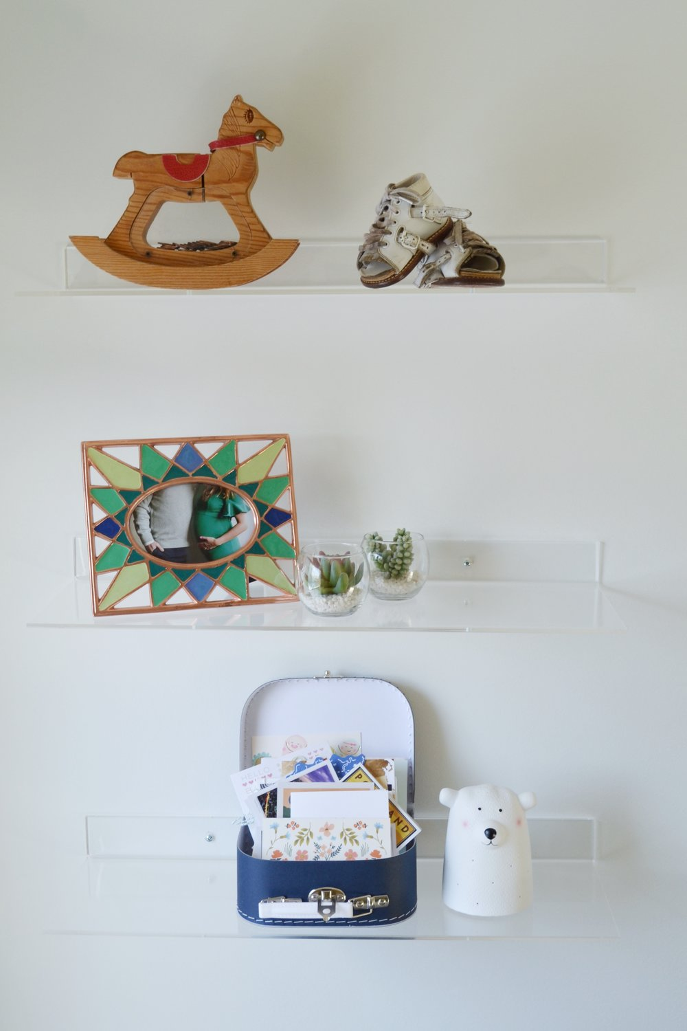 Nursery Shelves housing mementos from our childhood, a photo from our maternity shoot and cards from my baby showers.