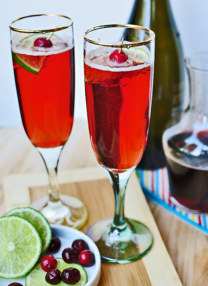This festive and pretty cranberry and pomegranate-infused syrup, mixed with bubbly (or soda water) and a squeeze of lime is the perfect sparkling drink to celebrate Christmas or toasting in the New Year.  Makes 12 drinks    Ingredients   1/2 cup unsweetened 100% cranberry juice 1/2 cup unsweetened 100% pomegranate juice 3/4 cup sugar Prosecco/Champagne or Soda water Fresh limes Whole cranberries and slices of lime for garnish, optional   Instructions   To make the simple syrup: In a small pan, stir together fruit juices and sugar (reduce the sugar if you prefer your drinks less sweet). Heat gently and bring to a boil. Turn to low and simmer for 5 minutes, stirring until sugar has dissolved. Pour the syrup into a jar and cool completely before storing in the refrigerator.  Assemble your tipple:  Pour 1.5 tbs (or to taste) of your cranberry-pomegranate syrup into a champagne flute. Top with Prosecco, Champagne or Soda water and squeeze in a wedge of lime. If you want to show off, add the garnish, using a toothpick skewer a whole cranberry and half a slice of lime before dropping it in.   Cheers…