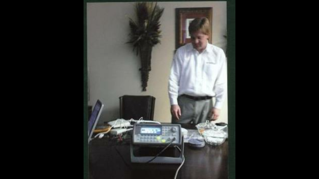 Dr. Charles standing over the CareLink medical Innovation Technology for Home Monitoring device