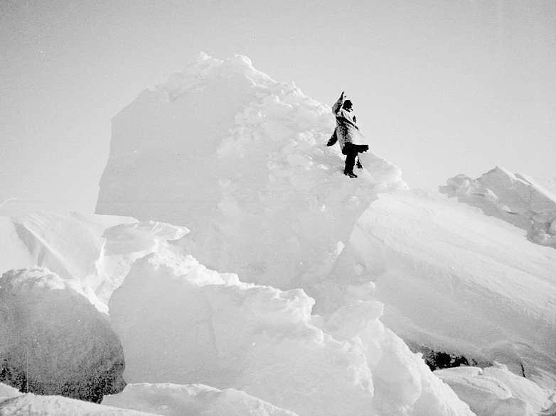 The late Inupiaq hunter, David Bodfish, climbs a massive ridge of piqaluyiq ice to scan the vast, frozen surroundings for polar bears.