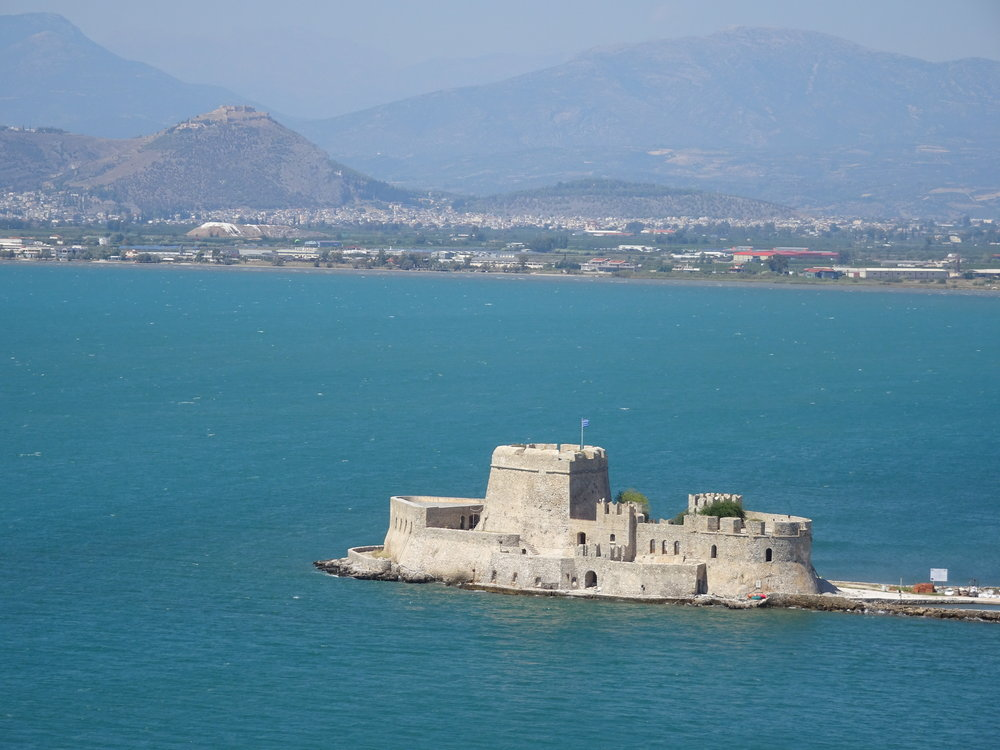 The small Venetian castle guarding Nafplia Bay from kitesurfers with the castle of Larissa on the hill above Argos in the background