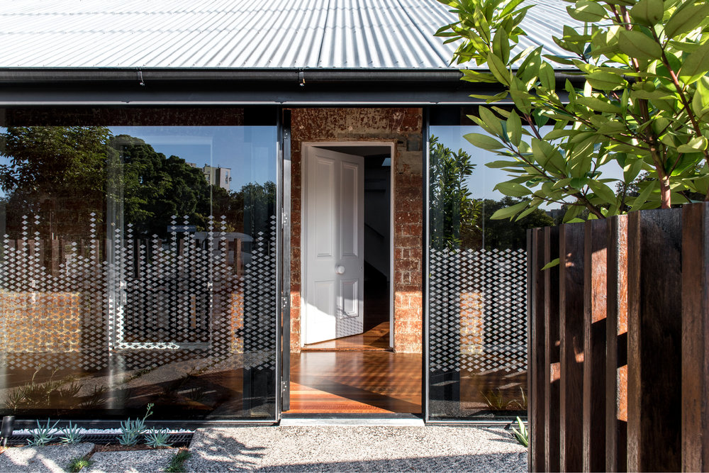 The tinted glass facade along the front verandahs creates a strong contrast to the heritage brick facade behind.