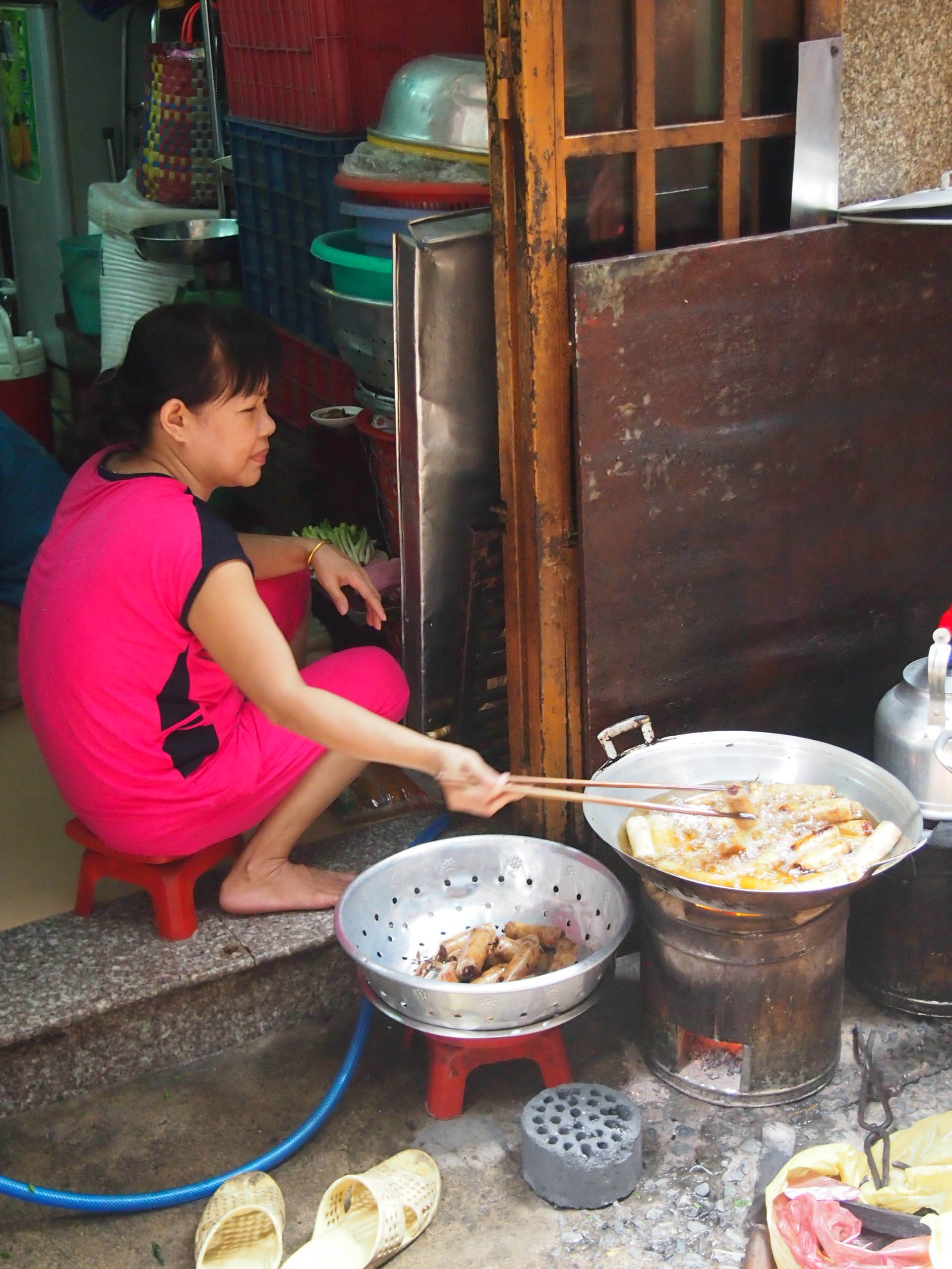 Exploring the alleyways in Ho Chi Minh City. The bottom floor of their home was kept open to do business, like this lady selling yummy fried things.