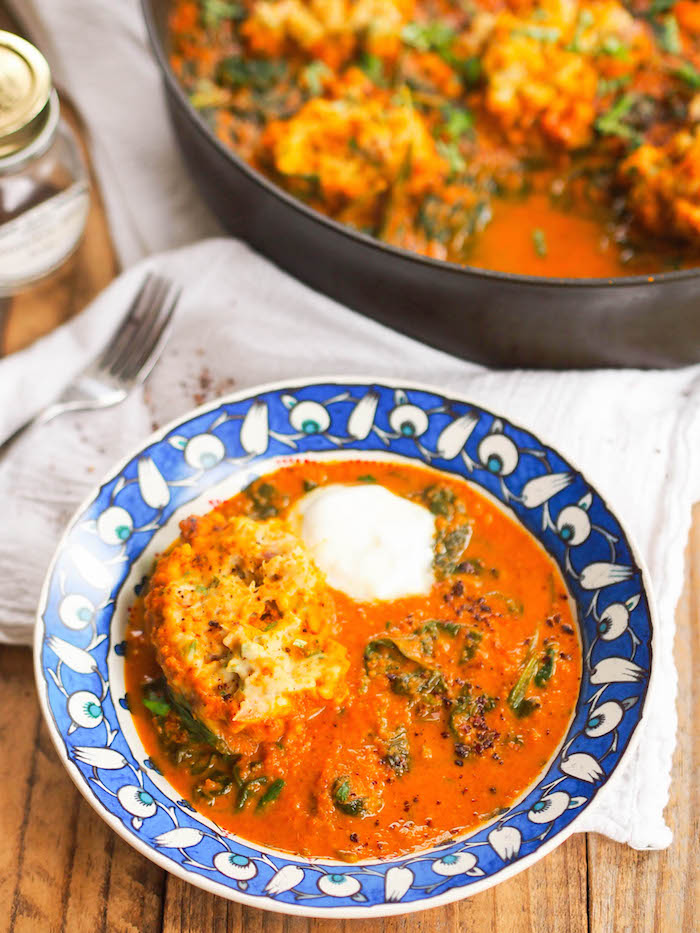 Vegetarian chickpea dumplings in a spicy Indian red curry sauce with coconut and spinach.