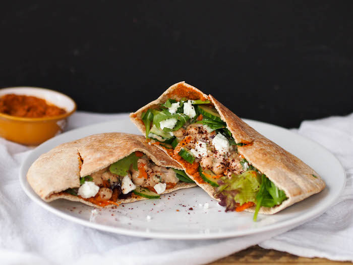 Easy yogurt and lemon zest chickpeas in a whole grain pita with veggies and red pepper-walnut spread