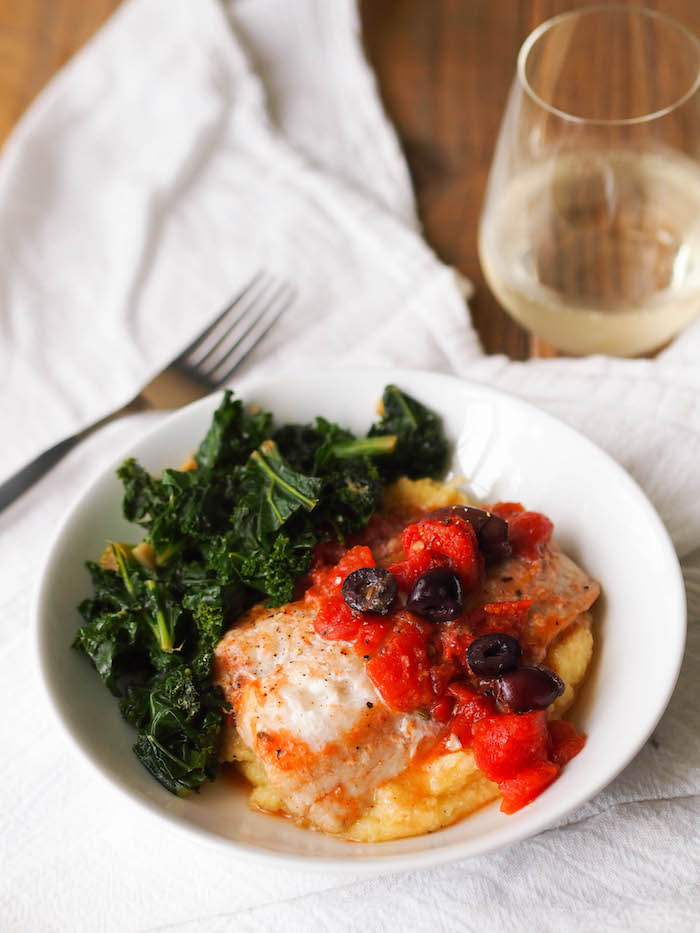 Greek Braised Cod with Tomatoes and Kalamata Olives served over creamy plenta with sauteed kale for a healthy Mediterranean inspired meal! #seafood #easyrecipe #healthyrecipe #glutenfree