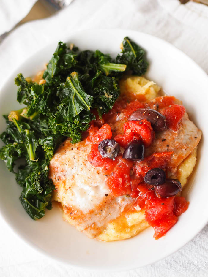 Greek Braised Cod with Tomatoes and Olives is a budget friendly Mediterranean dish! Serve over polenta with sauteed kale! #fish #seafood #mediterraneandiet #glutenfree