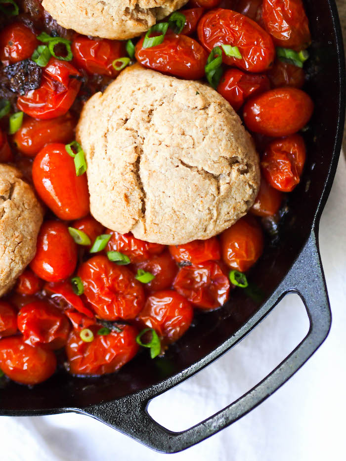 A savory tomato cobbler with sweet, caramelized onions and tomatoes, topped with flaky whole wheat yogurt biscuits