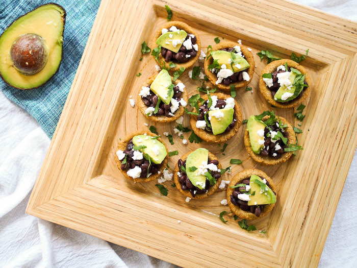 Vegetarian baked sopes filled with black beans, avocado and drizzled with salsa verde!