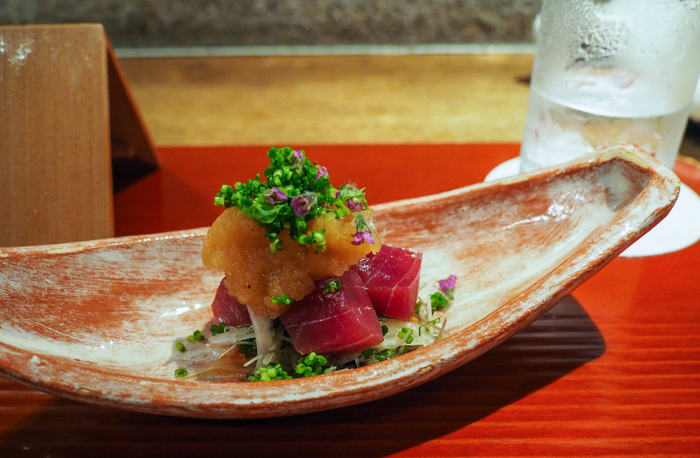 Tuna sashimi with grated radish and herbs over a crispy salad