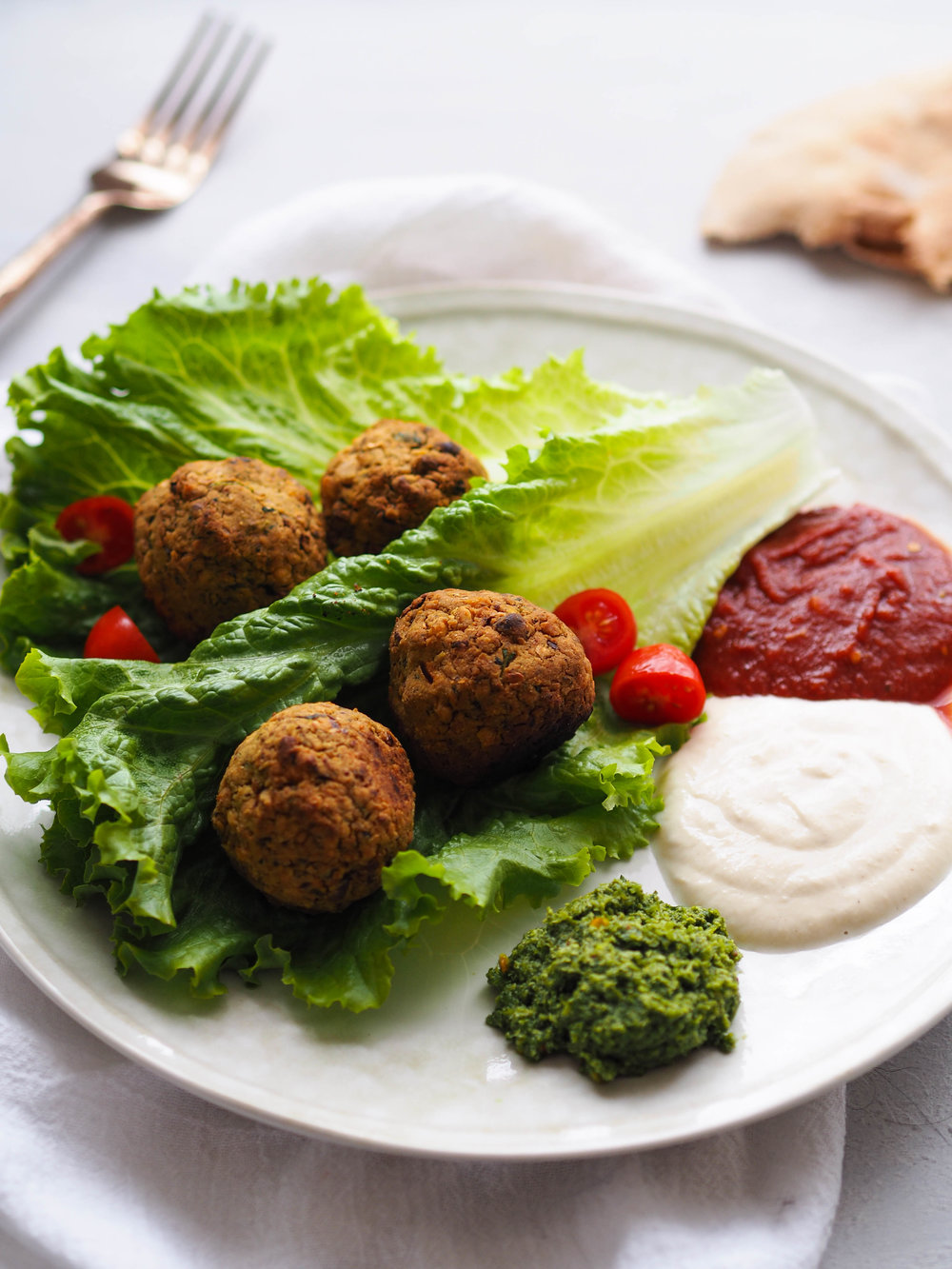 These easy baked green falafel are served with three different sauces - harissa tomato, tahini yogurt, and green chutney! #falafel #vegan #vegetarian #healthyrecipe