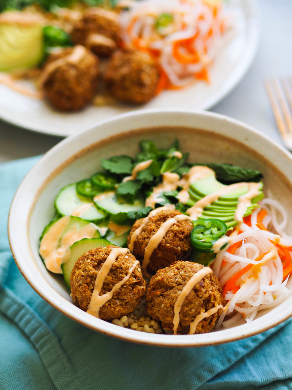 Banh mi in a bowl! Top brown rice with lemongrass tofu meatballs, pickled veggies and herbs, then drizzle with a spicy sriracha aioli! #grainbowl #tofu #Vietnamese #banhmi #healthyrecipe