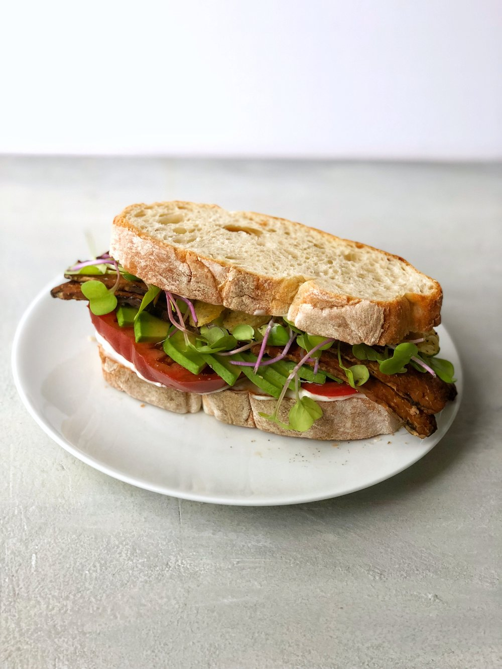 Heirloom Tomato Tempeh TBLTA! The most perfect of summer sandwiches gets an upgrade with tempeh bacon, avocado and crunchy kettle chips! #summer #sandwich #BLT #tomato #vegetarian #vegan