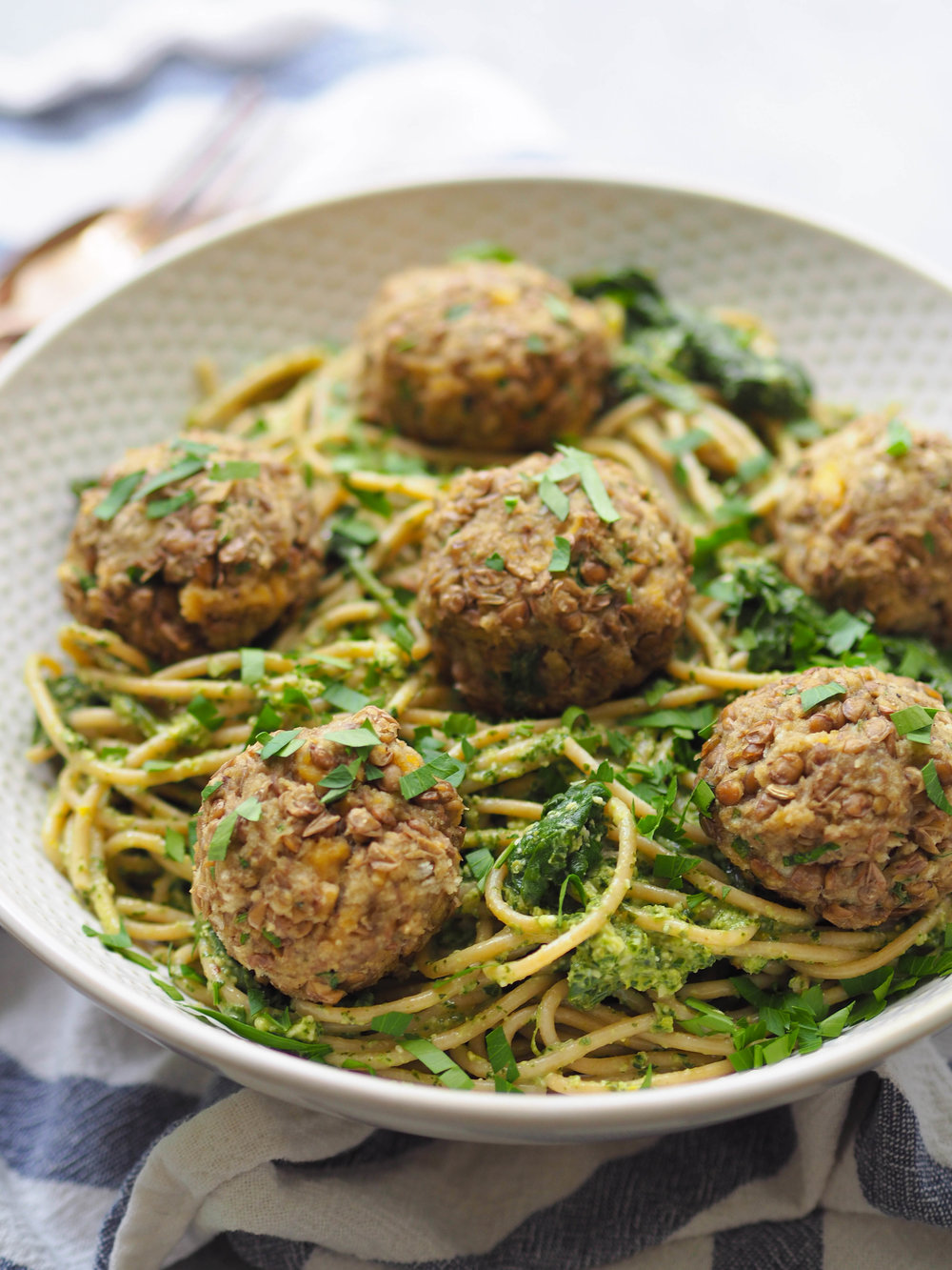 These vegetarian lentil meatballs are perfect over spaghetti and greens tossed with lemony pesto! #vegetarian #pasta #lentils #healthyrecipe