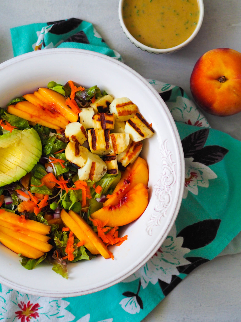 Make this summery grilled halloumi and peach salad with lemon-tahini dressing! Easy and packed with fresh flavor! #salad #vegetarian #healthyrecipe #halloumi #peach #summer