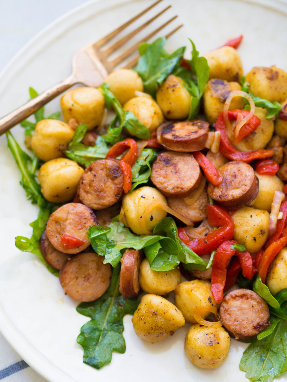 Pan-fried gnocchi and chicken sausage salad is just as good as it sounds! With roasted red peppers, arugula and quick pickled shallots! The best 30 minute meal! #quickrecipe #gnocchi #pasta #easydinner #salad