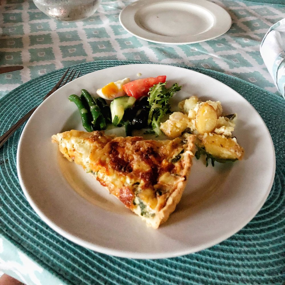 A yummy veggie quiche with potato salad and a deconstructed nicoise salad