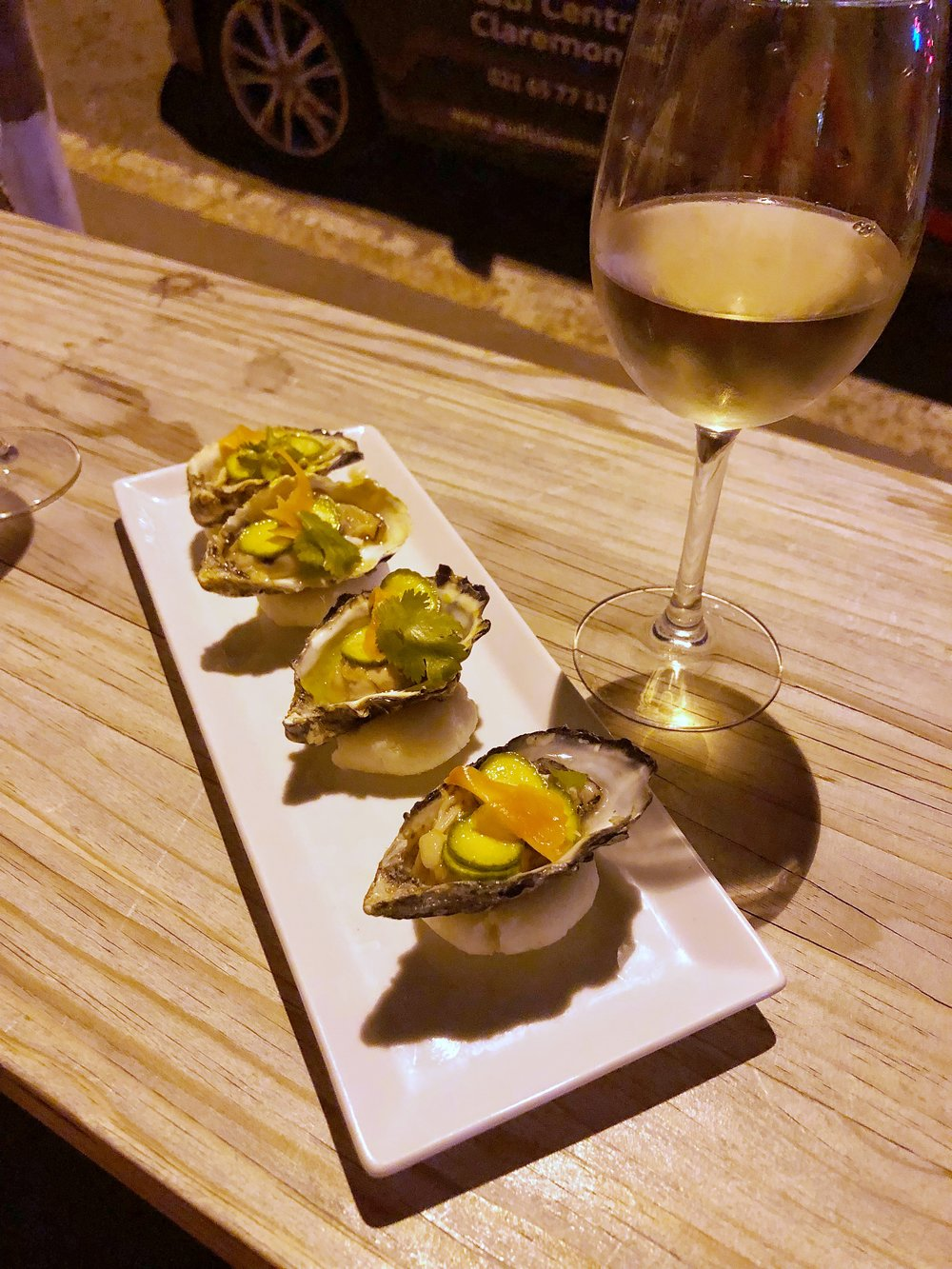 Raw local oysters with wasabi cream, pickled cucumber and ginger, and cilantro
