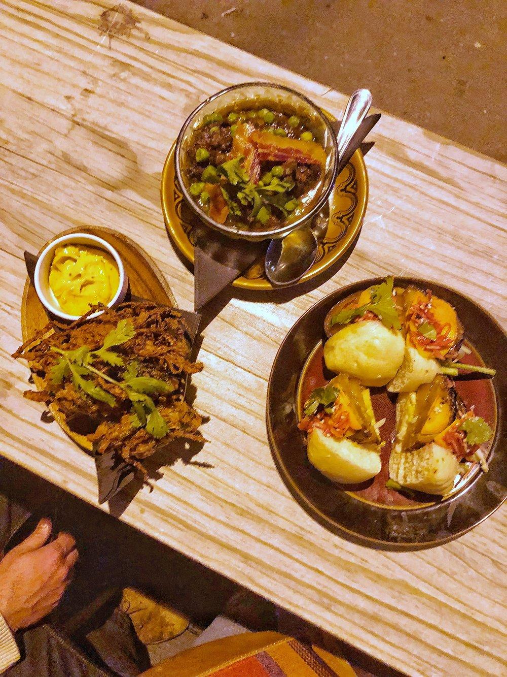 Onion bhajis and atcha mayo, braised springbok with peas and crispy bacon over potato mash, steamed bao with pickled eggplant and tahini sauce
