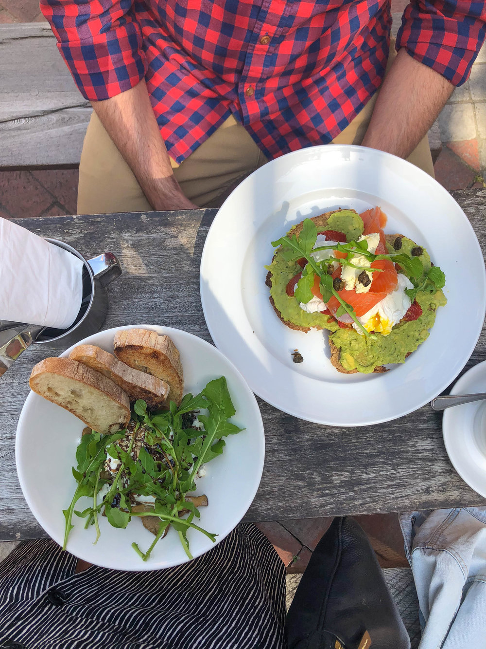 Breakfast at Saucisse: breakfast bowl with poached eggs, lemony spinach, sauteed wild mushrooms, arugula, and super creamy feta, and smoked salmon avocado toast on macadamia nut bread